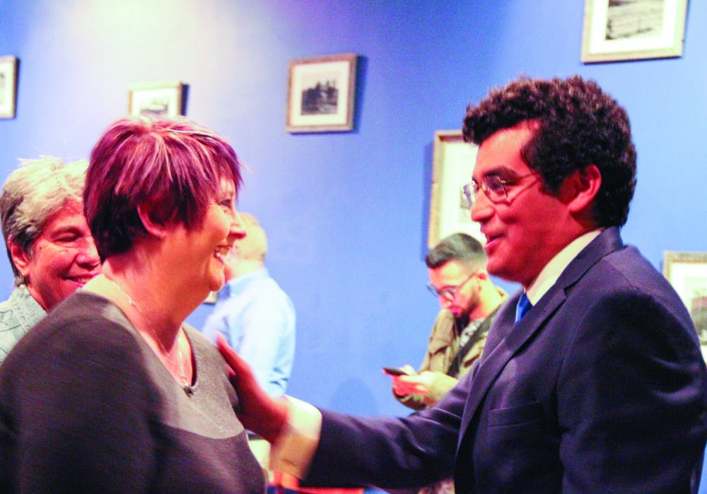 "<p dir=""ltr""><span>From left: Lisa Marshall congratulates David Arreola, 26, on his District 3 win Tuesday night at a results watch party at Blue Gills Quality Foods.</span></p><p><span> </span></p>"