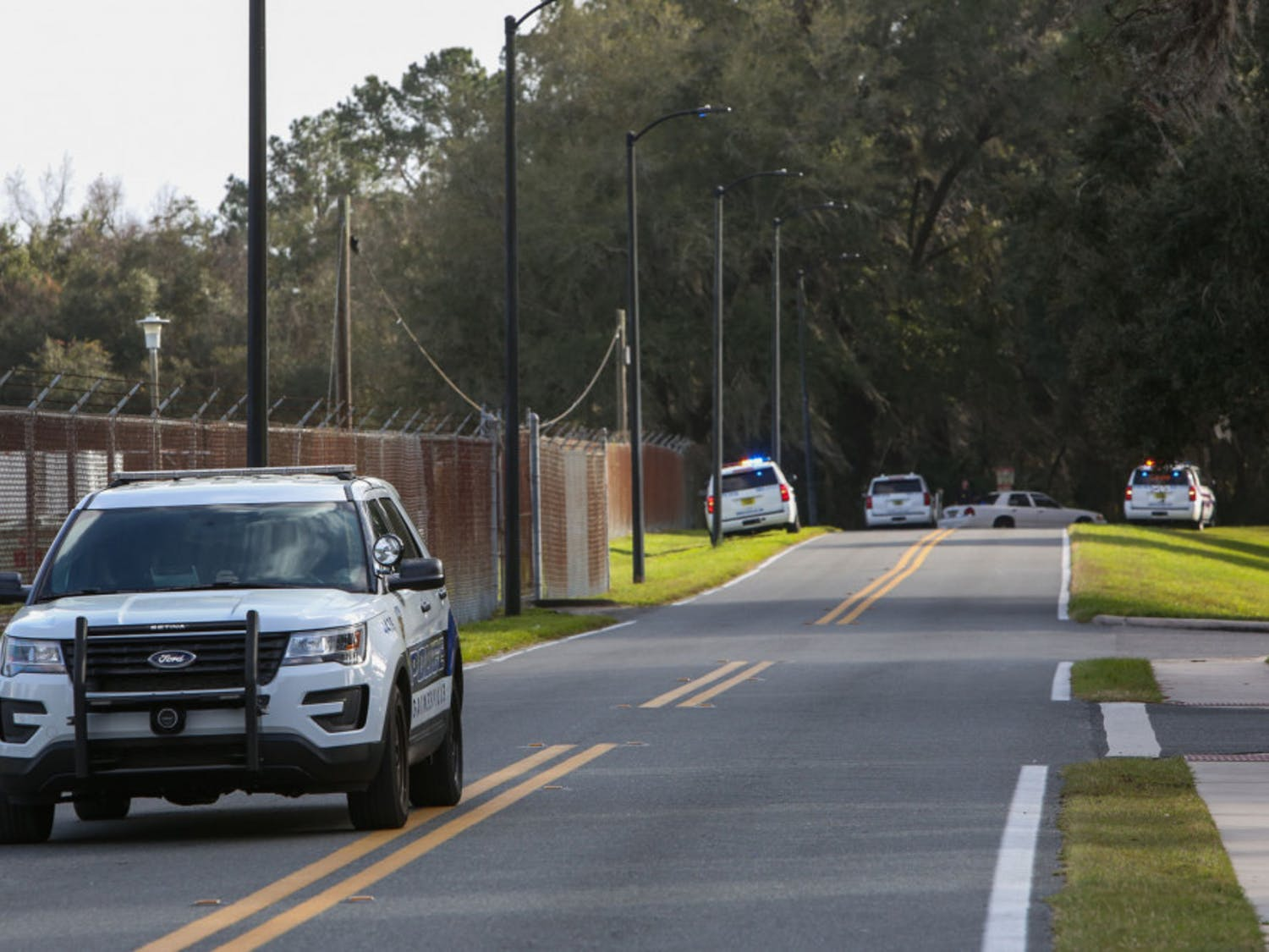 A University of Florida Police Department officer leaves the scene in a vehicle Friday while officers search a wooded area near the UF College of Veterinary Medicine for a suspect reportedly firing a gun at targets.