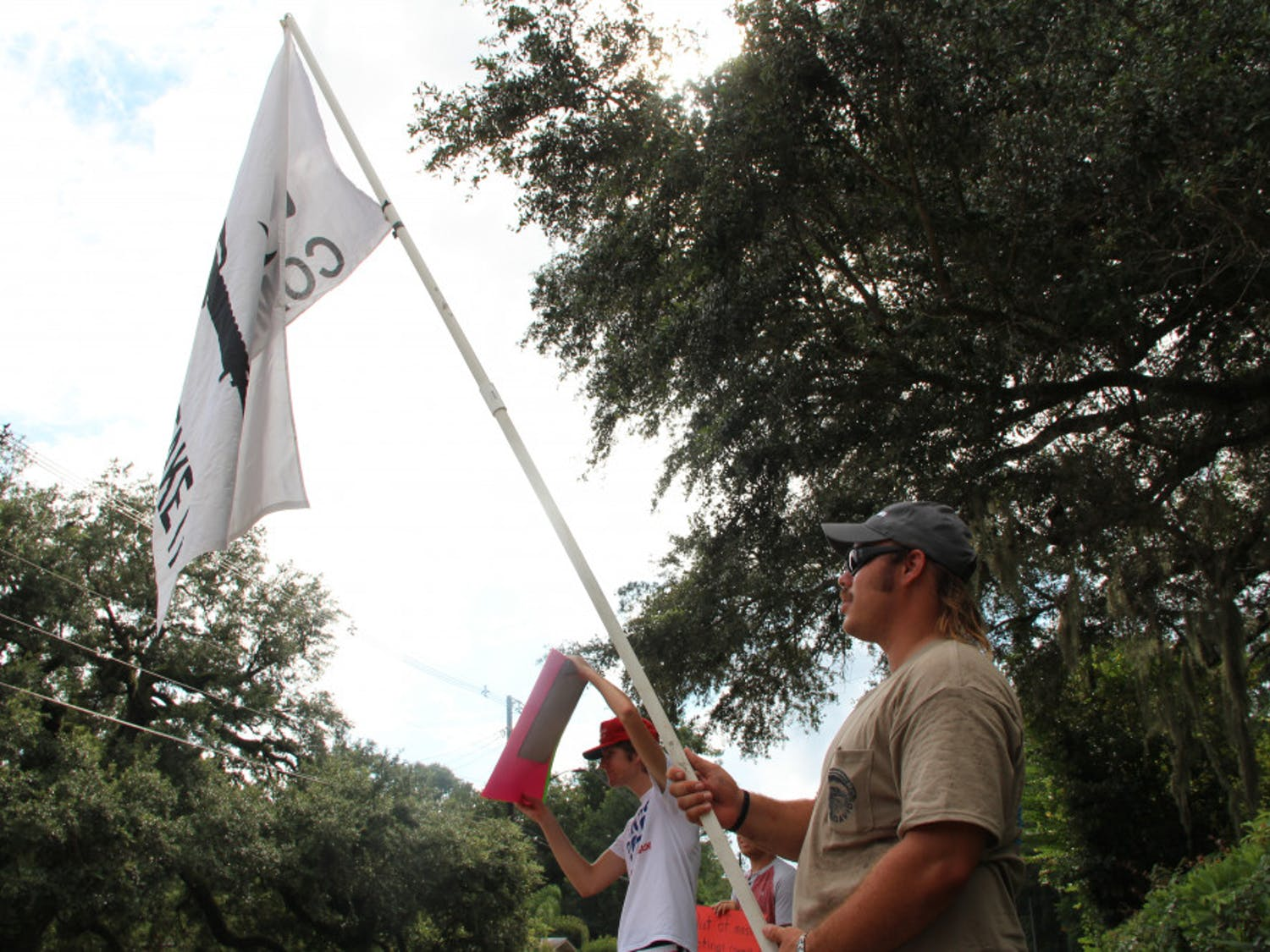 """Libertarian party member Chris Rose II (right), 29, waves flag with the words """"Come and Get It"""" printed next to a firearm with to 21-year-old Taylor Wyatt Foland (left). The two protested across the street from the Gainesville Women's Club during the March For Our Lives panel."""