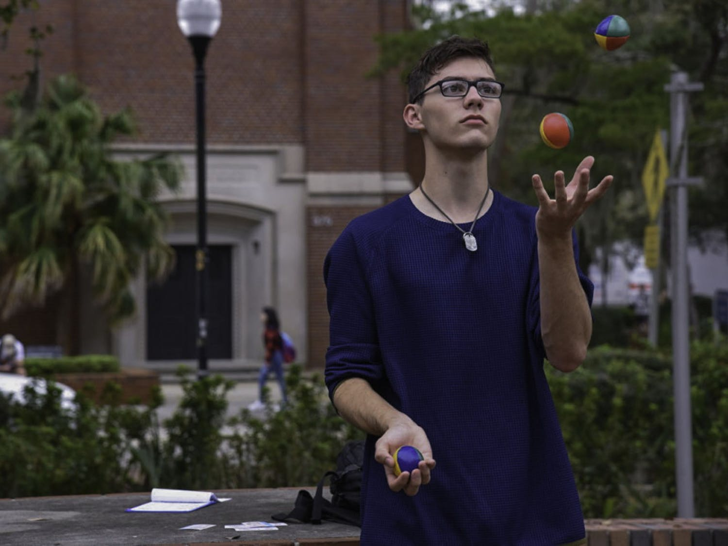 "Ethan Irvin, a 19-year-old UF mathematics sophomore, juggles on Turlington Plaza on Feb. 12. Irvin said he's been juggling for more than two years and loves doing it. ""It's a good stress reliever,"" he said."