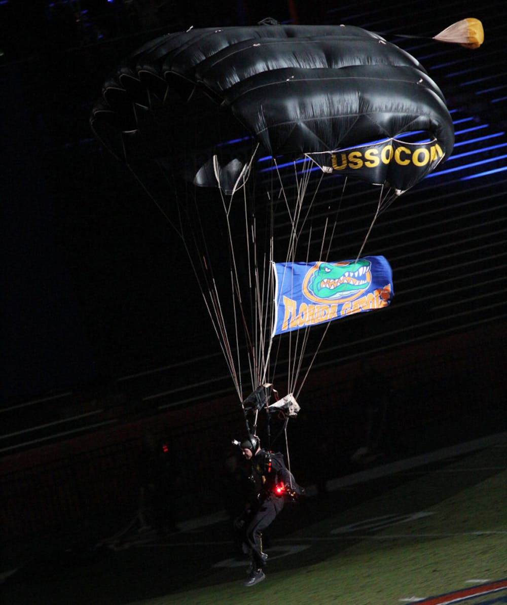 <p>A member of the Para-Commandos skydiving team lands on Florida Field at Ben Hill Griffin Stadium during Gator Growl on Friday night.</p>