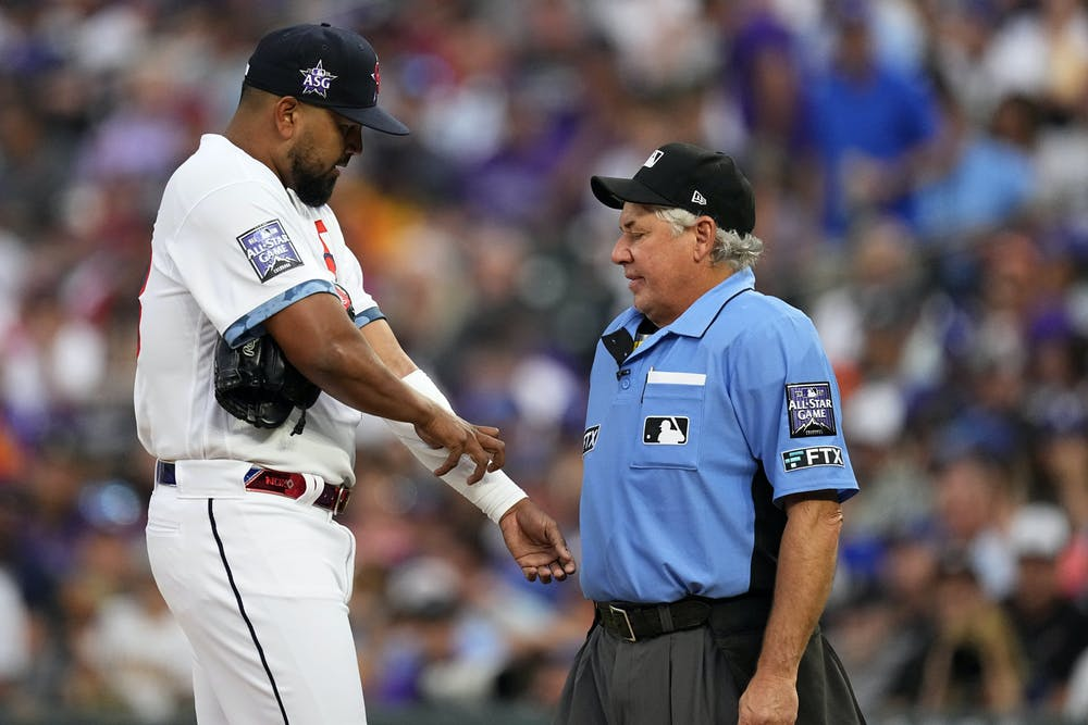 Home plate umpire Tom Hallion, right, checks for foreign substances on National League's German Marquez, of the Colorado Rockies, during the fourth inning of the MLB All-Star baseball game, Tuesday, July 13, 2021, in Denver. (AP Photo/Jack Dempsey)