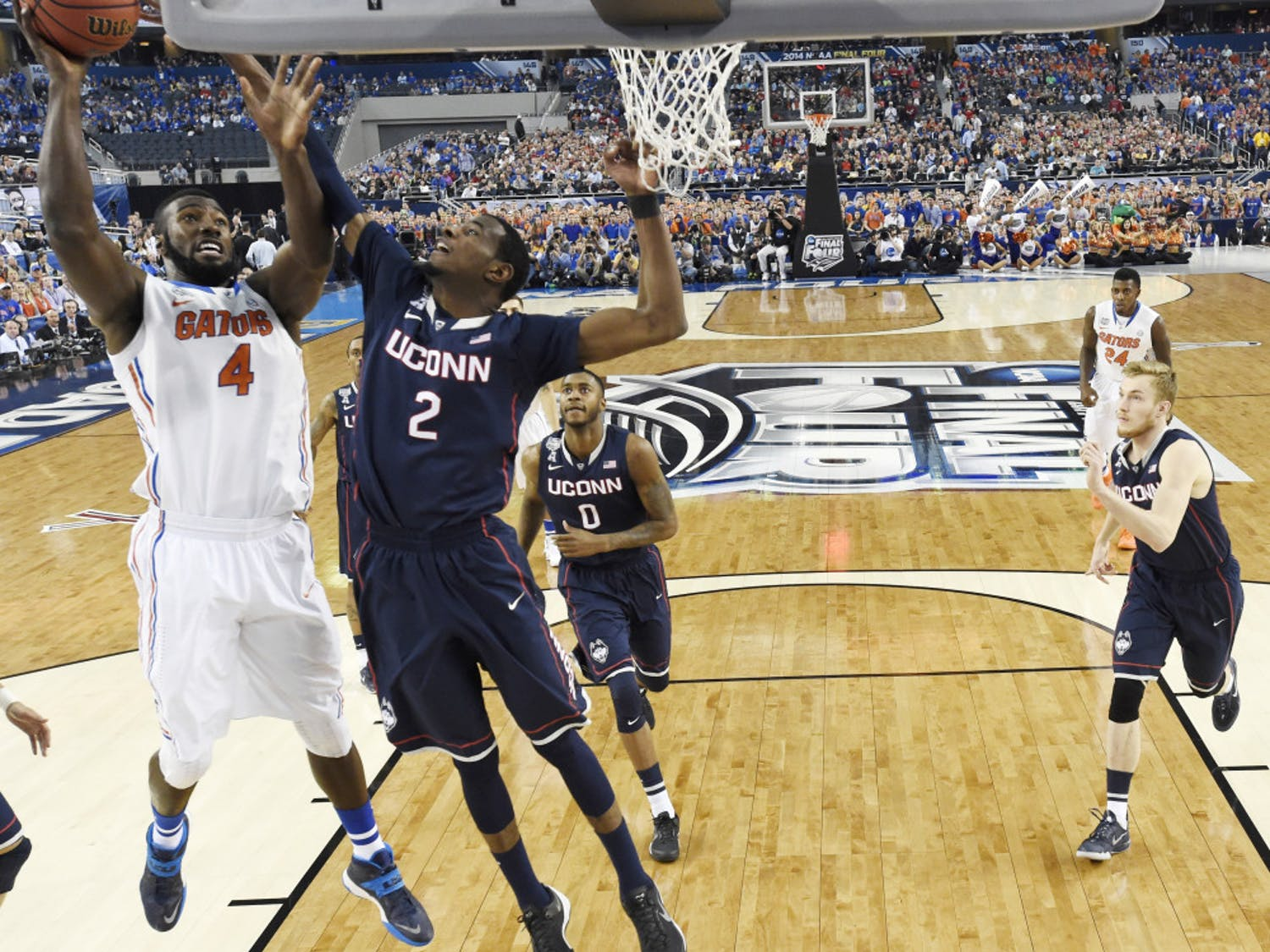 Florida center Patric Young (4) drives to the basket past Connecticut forward DeAndre Daniels (2) during the first half of the NCAA Final Four tournament game on Saturday in AT&T Stadium in Arlington, Texas.