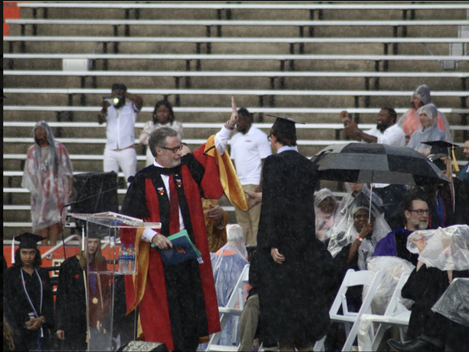 College of Liberal Arts and Sciences Dean, David Richardson, gestures to pause the commencement ceremony. Richardson announced the ceremony would be delayed by 30 minutes, but the ceremony was later moved to an inside hallway of the stadium.