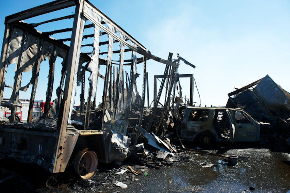 <p>The charred wreckage of a semitrailer and an SUV sit on Interstate 75 in Paynes Prairie Preserve State Park on Jan. 29, 2012. Today marks the one-year anniversary of the accident that claimed the lives of 11.</p>