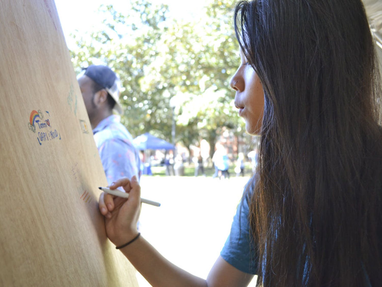 """Natalie Heller, a 20-year-old finance junior, writes her name on the door at National Coming Out Day on the Plaza of the Americas on Oct. 12, 2015, to support coming out. Heller said writing her name on the door meant not being afraid. """"If someone were to walk by and see my name, I wouldn't care,"""" Heller said. """"The same time last year I wouldn't have been willing to."""""""