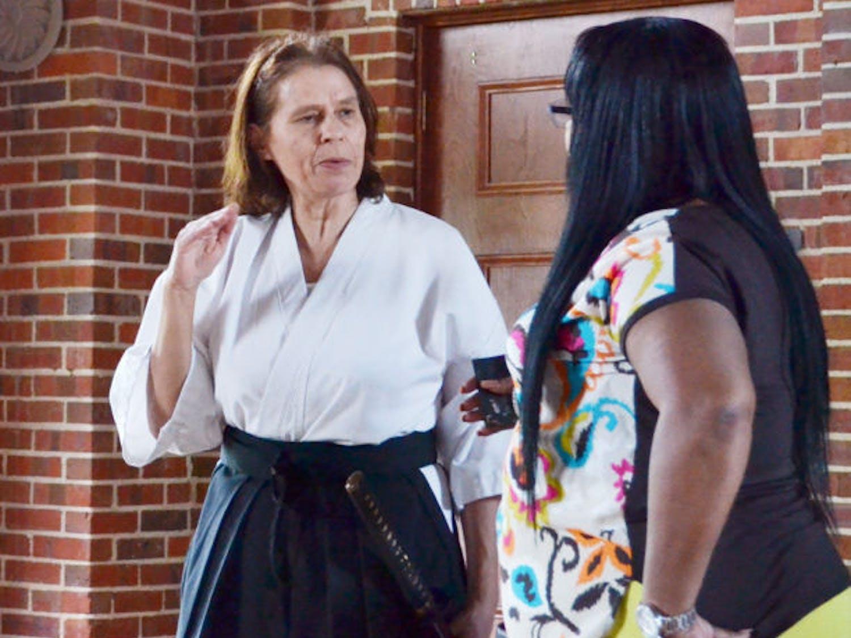 "Santa Fe College student Velinda Davis talks to artist Sheila Barksdale on Saturday at the Archer Community Center at the ""Interpreting the Sword"" event."