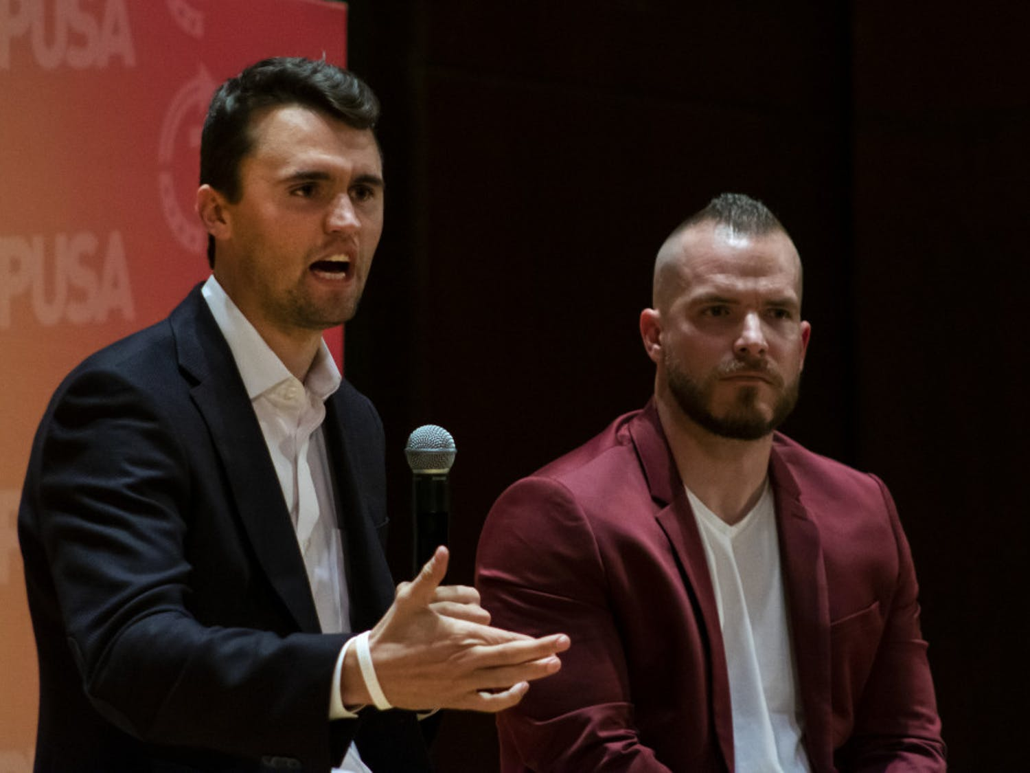 Charlie Kirk, leader of Turning Point USA, and Graham Allen, political speaker, answer questions from the audience Tuesday night in University Auditorium. Many of Kirk's answers were met with a mixture of cheers and boos from the crowd.