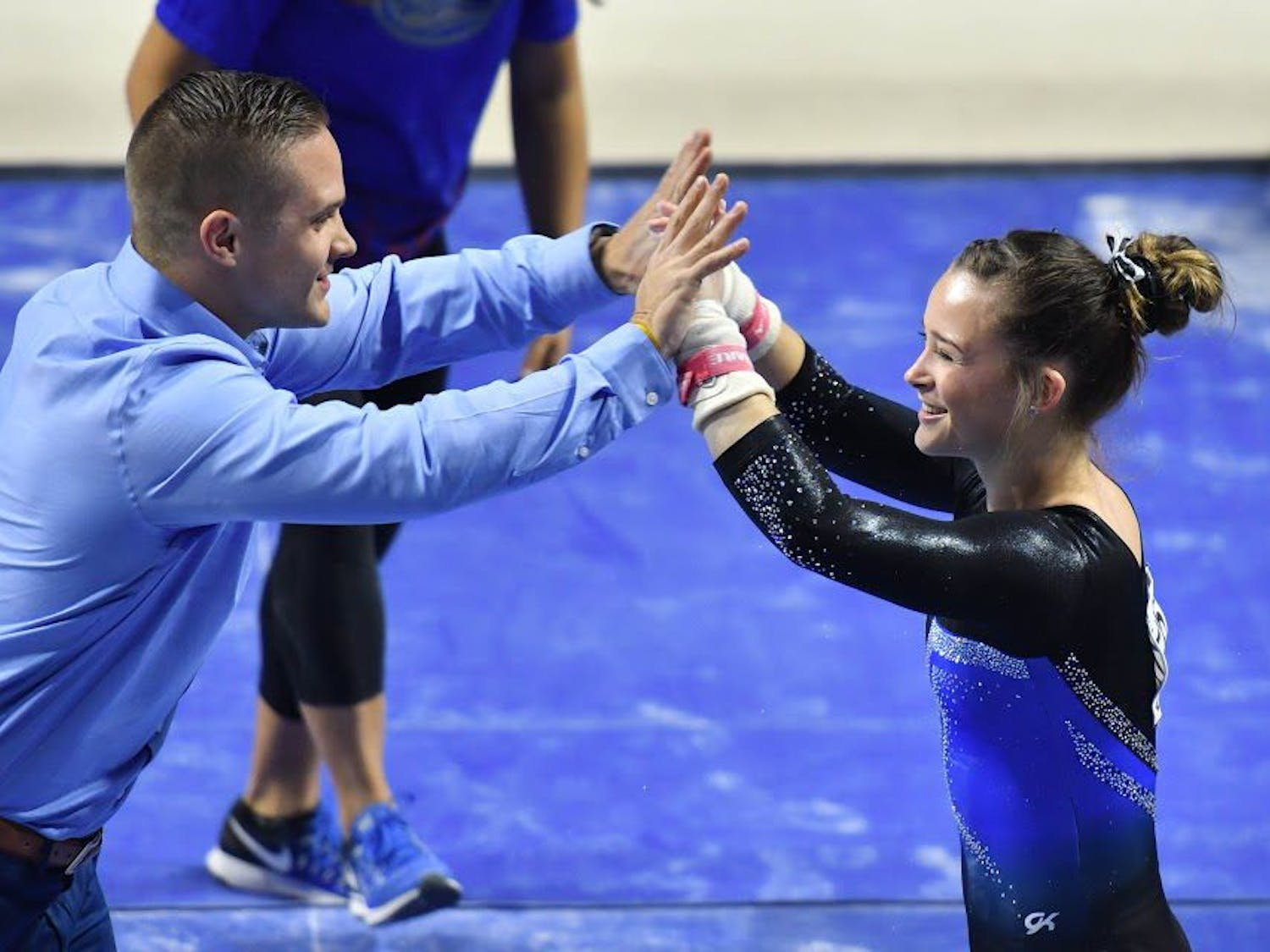 Florida assistant coach Owen Field high fives UF gymnast Maegan Chant during the NCAA Gainesville Regional on Saturday in the O'Connell Center.