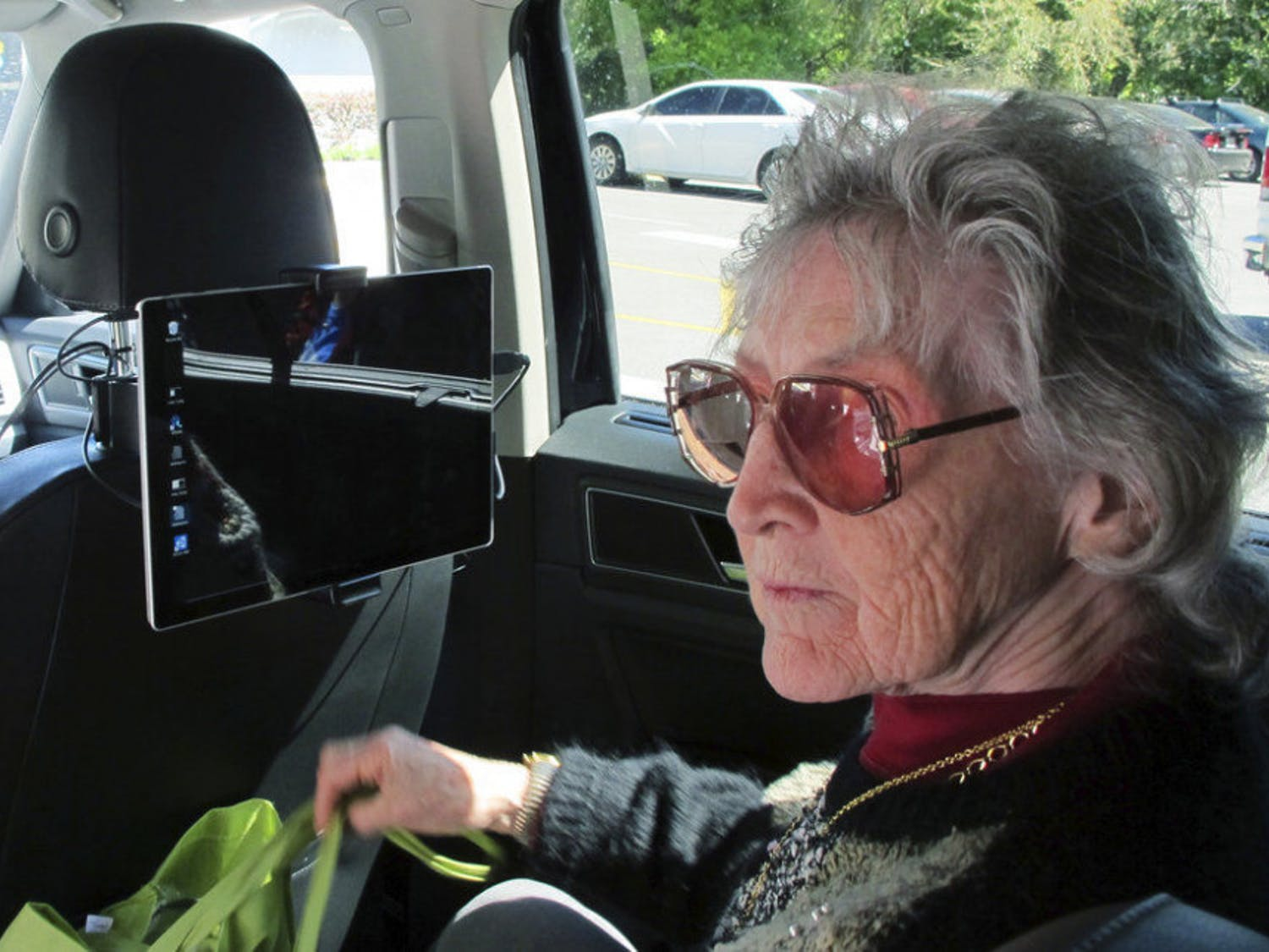 In this photo taken Wednesday, March 7, 2018, shows Sharon Van Etten, listening to a computerized voice in a vehicle equipped with software meant to help the visually impaired interact with self-driving cars in Ocala, Fla. Six years after a video went viral of a blind man going through a drive thru in a self-driving car, advocates for visually impaired people worry the industry is leaving them behind as they develop the cars of the future. So prominent groups are turning to university researchers like Brinkley to help build systems that will unlock the potential of autonomous cars' for the blind.