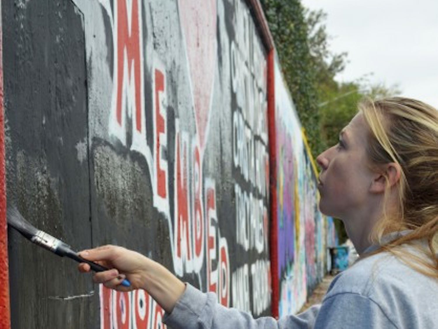 """Brianna Rubel, 25, restores a memorial for the victims of the Danny Rolling murders on the 34th Street Wall. She decided to help another artist paint over hateful comments in the """"remember"""" section Tuesday."""