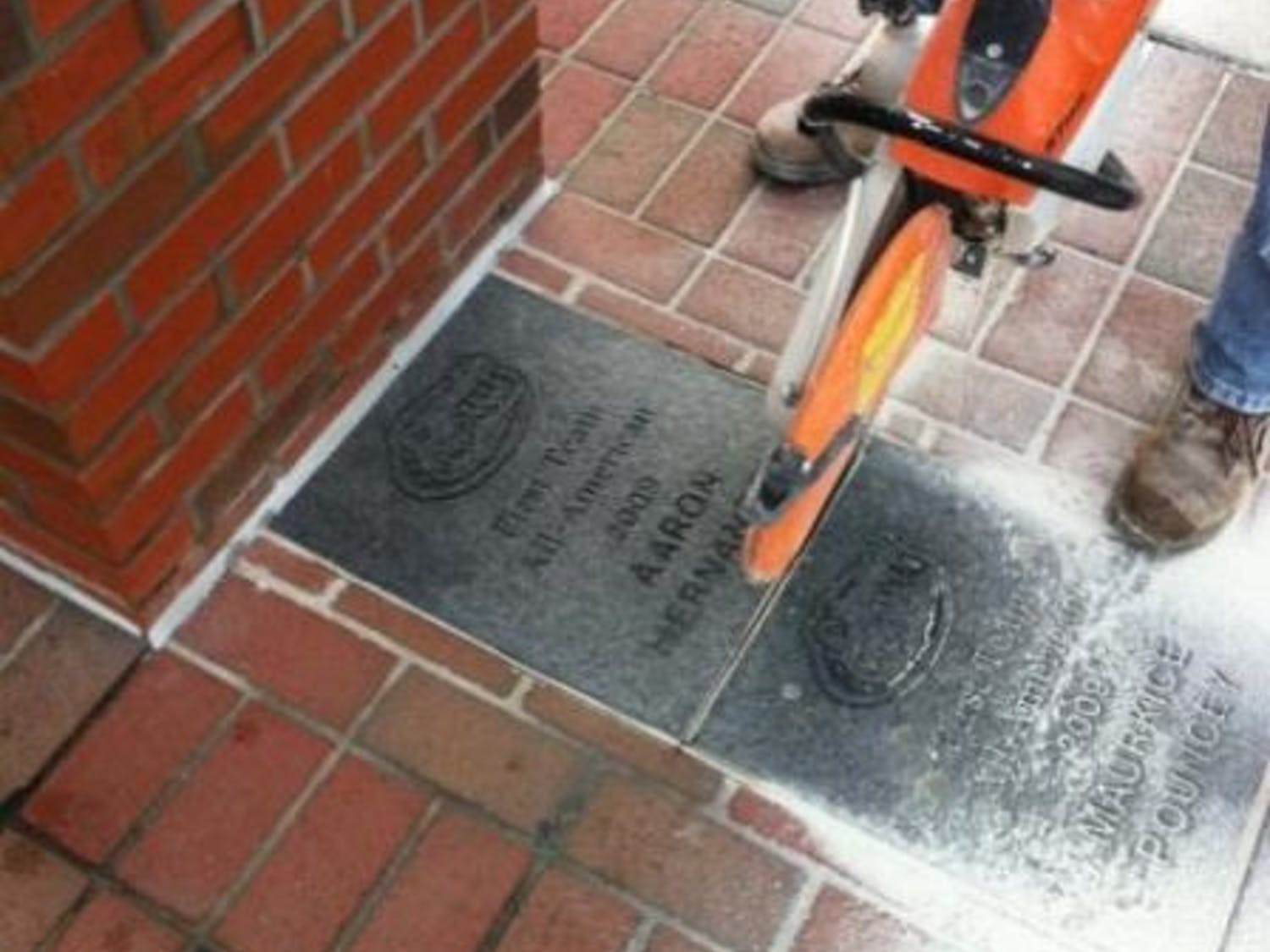 """Aaron Hernandez's All-America brick is removed from outside the James W. """"Bill"""" Heavener Football Complex on Thursday. UF decided to remove the brick while the former UF tight end faces murder charges.  Ed. note: The caption originally misstated the location of the brick in one location. It is not at Gator Walk, but outside the Heavener Football Complex."""