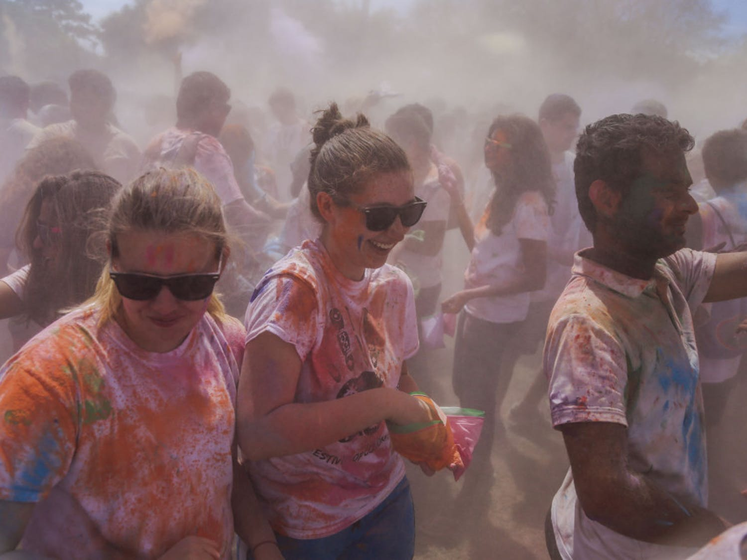A group of students laugh as more than 1,000 people throw paint during the UF Holi Festival of Colors on Sunday.