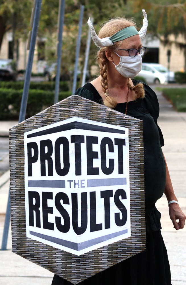 """A picture of Sarah Younger holding a """"Protect the Results"""" shield"""