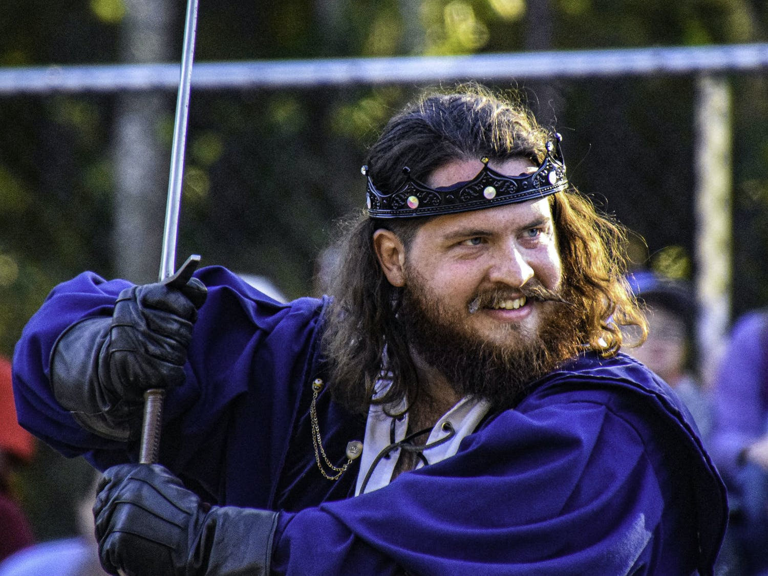 Cody Ward, a 29-year-old actor with volunteer acting troupe Thieves Guilde, brandishes a sword to play-fight an opponent during a life-sized game of chess at the Hoggetowne Medieval Faire.