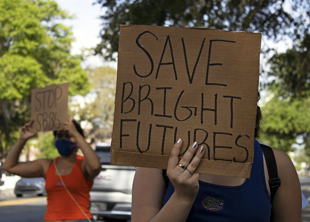 """Aleidys Lopez (right), 19, a sustainability studies and women's studies sophomore shields her face from the sun with a """"Save Bright Futures"""" sign as she and three other protestors march down University Avenue on Friday, March 26, 2021. The protest was held to raise awareness about Senate Bill 86, which was amended on Tuesday."""
