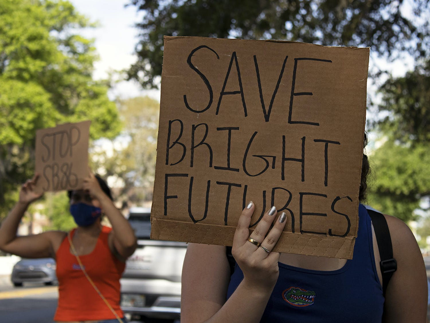 "Aleidys Lopez (right), 19, a sustainability studies and women's studies sophomore shields her face from the sun with a ""Save Bright Futures"" sign as she and three other protestors march down University Avenue on Friday, March 26, 2021. The protest was held to raise awareness about Senate Bill 86, which was amended on Tuesday."