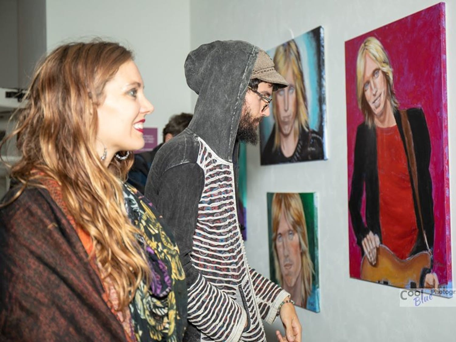 Two attendees at Friday night's reception for the Matheson's new Tom Petty exhibit look at paintings of the musician created by local artist Barbara Tench.
