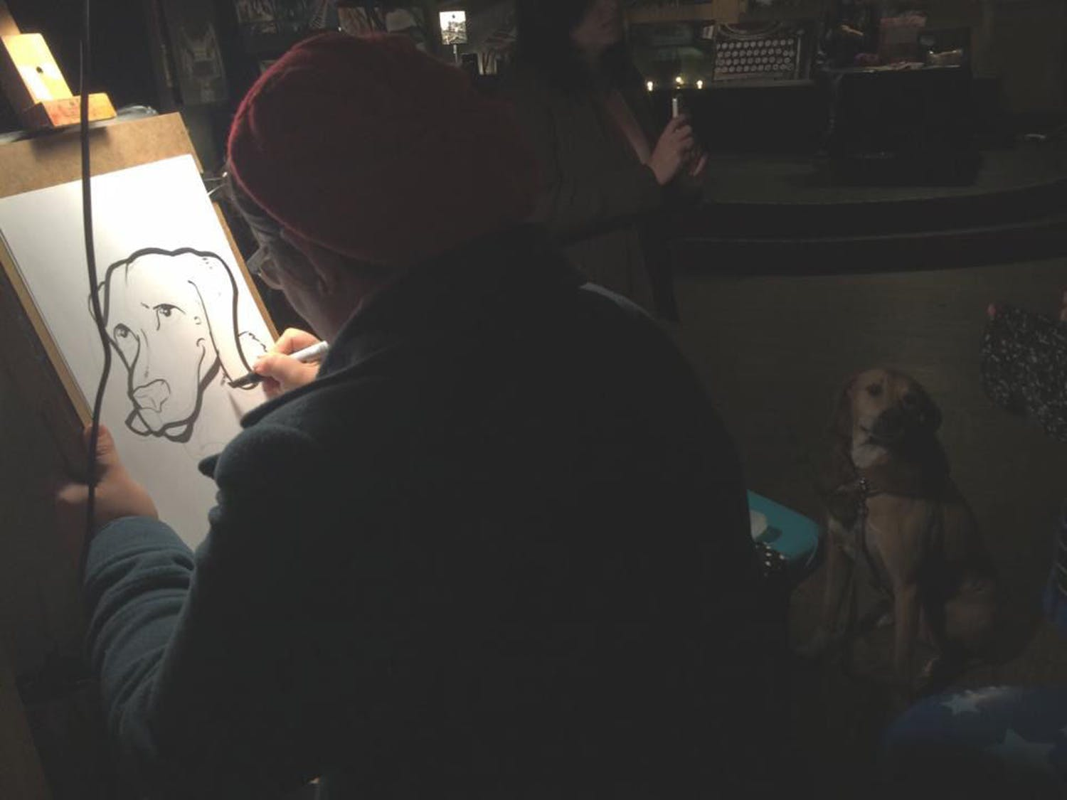 Local caricature artist Corinne Halley draws a caricature of a patron's dog during February's Art Attack at High Dive, 210 SW Second Ave. High Dive's Art Attack will be part of Artwalk Gainesville for the first time on Friday. While the event is free, donations are welcomed to keep the event free of charge for its patrons and vendors.