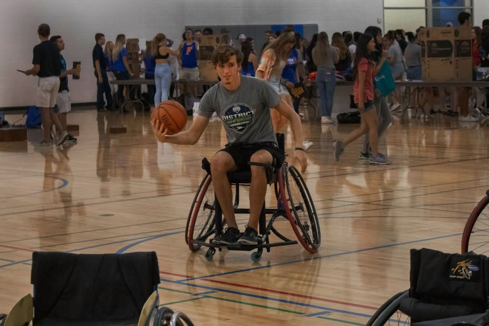 """<p dir=""""ltr""""><span>TJ Comer, an 18-year-old wildlife ecology freshman, plays wheelchair basketball Thursday evening as part of the Inclusivity project at RecSports. Every other semester, wheelchair basketball is offered as a sport for UF students to compete in. Students who aren't handicapped are encouraged to join to raise awareness for disabilities and to understand people who have disabilities. """"It's a lot harder than I thought it would be,"""" Comer said. """"But eventually I got used to it."""" He said he was planning on joining intramural basketball and flag football but is now considering joining wheelchair basketball.</span></p>"""
