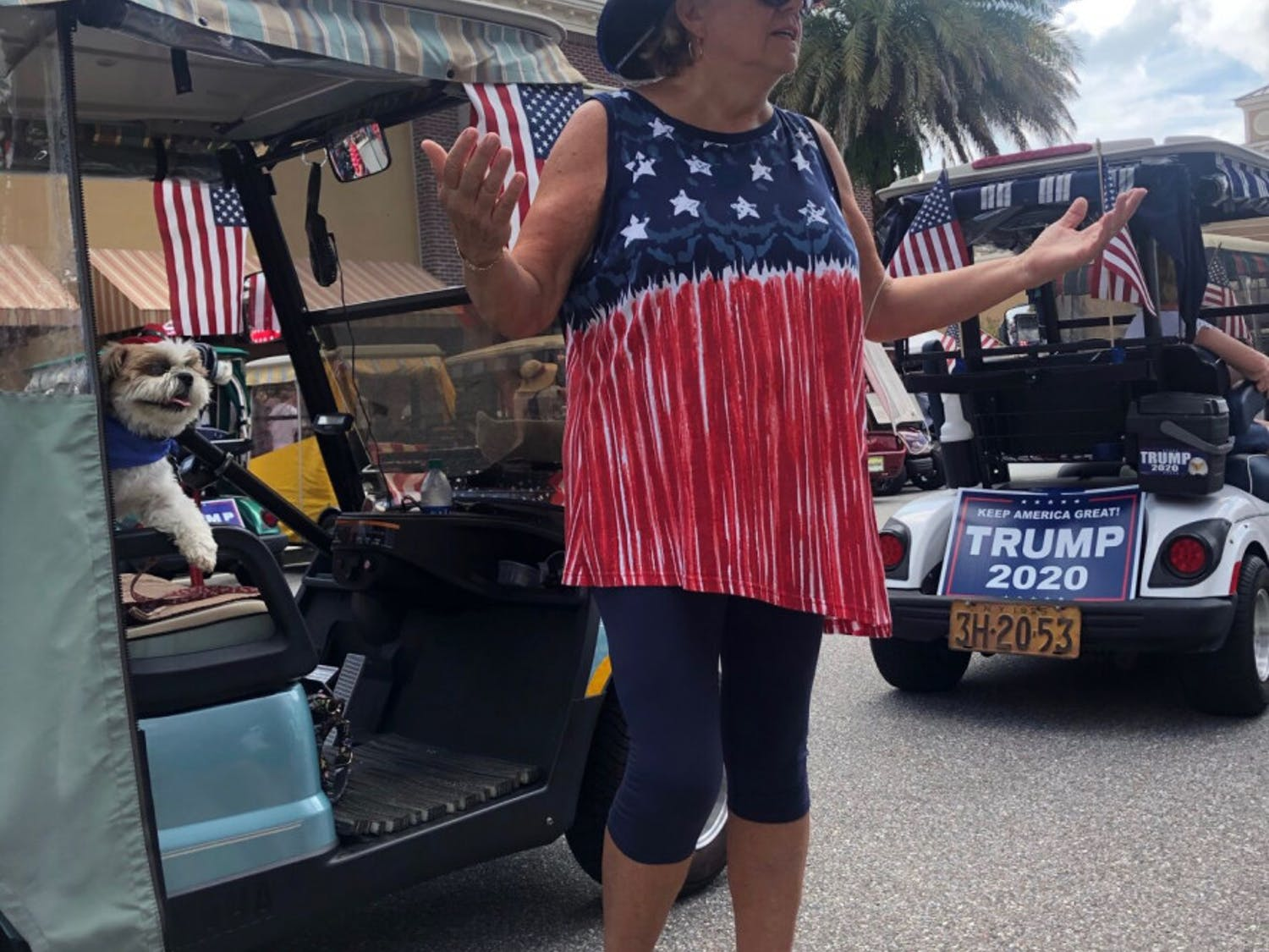 Kathy Slattery, 69, and her dog Samson, 8, waited to enter the event in a line of golf carts waving Trump flags.