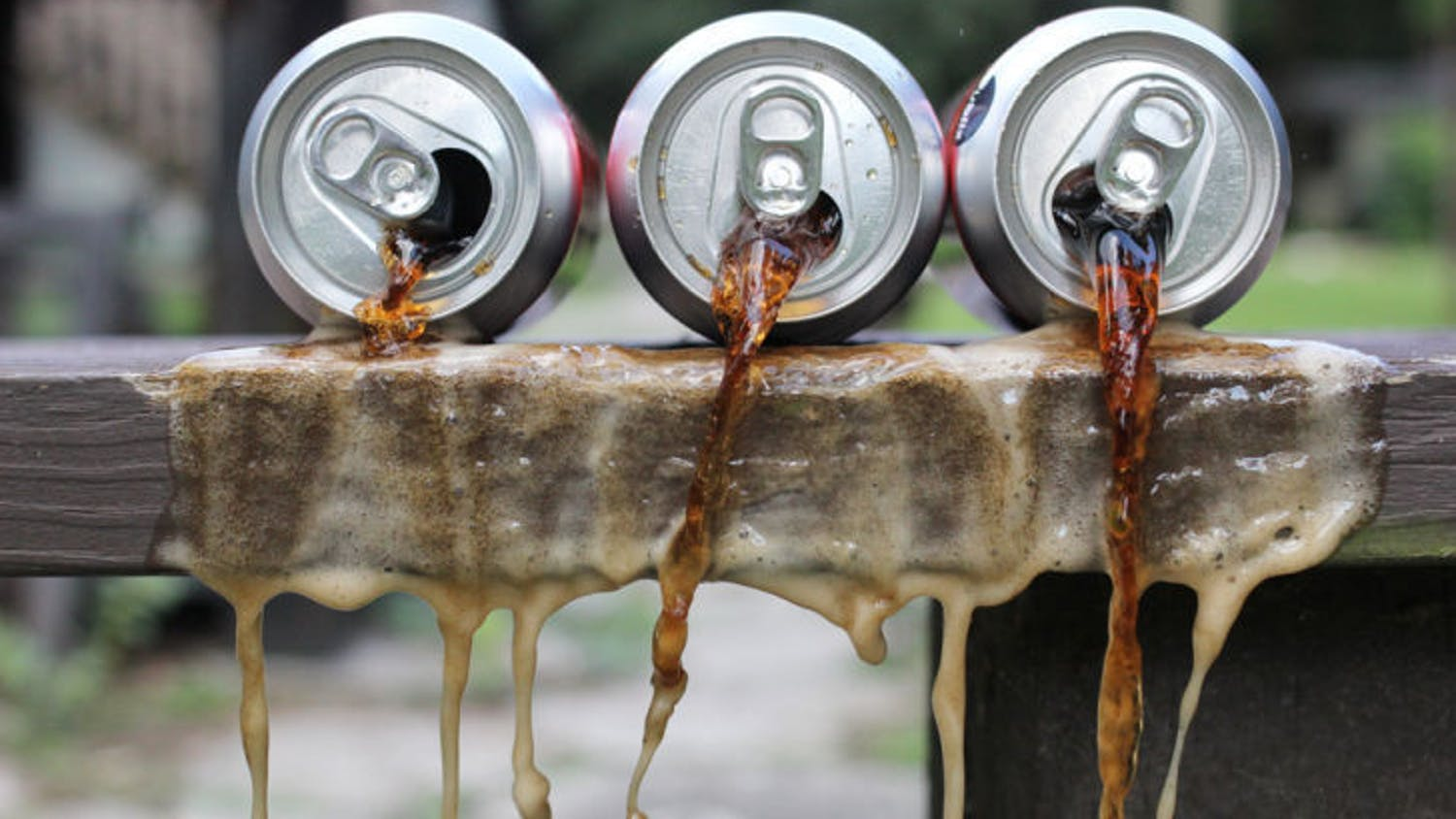A set-up photo shows soda spilling out of cans. A recently published study suggests that the alertness experienced after drinking sugary beverages is actually more of a placebo effect than the effect of the sugar.
