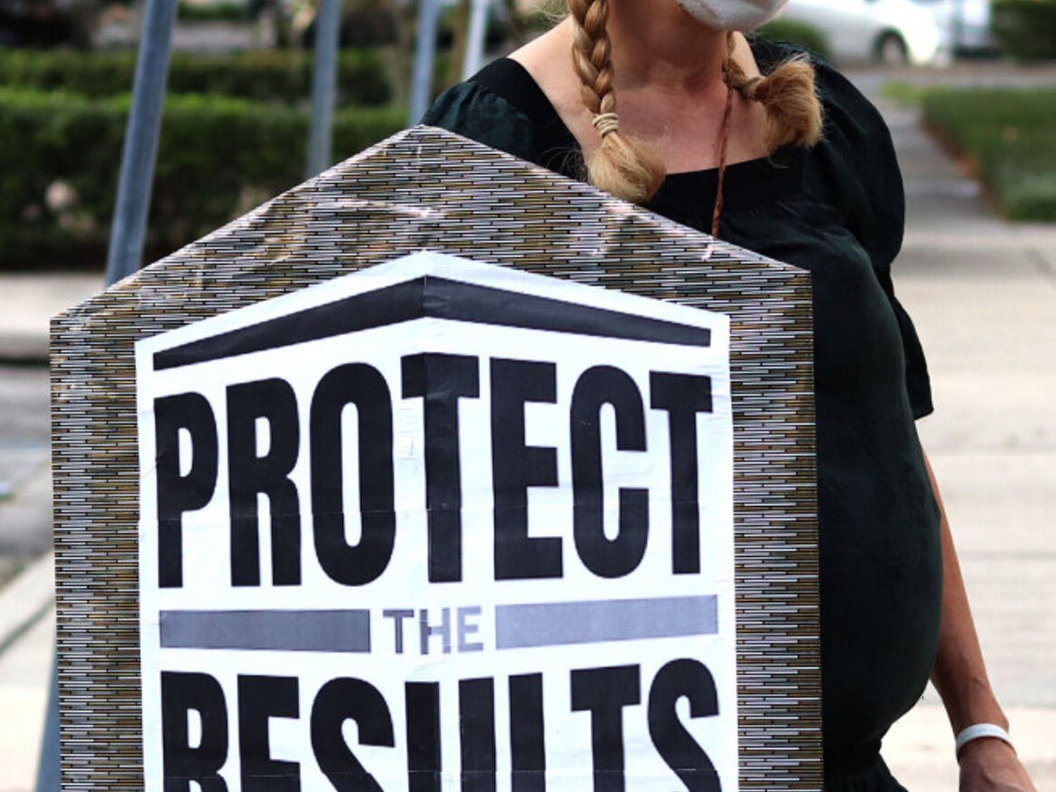 """Sarah Younger holds a shield stating """"Protect the Results"""" during the rally held at the Alachua City Hall on Wednesday, Nov. 4, 2020. Younger said, """"It ain't over 'til the fat lady sings, and I'm not singing yet."""" (Lauren Witte/Alligator Staff)"""