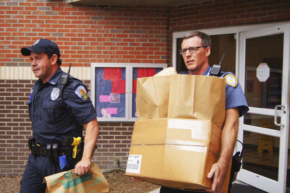 """<p class=""""p1"""">A University Police Department officer, left, and a Gainesville Police public service technician transport evidence bags to a GPD forensic crime unit vehicle at the Springs Residential Complex at about 2:30 p.m. Monday. The residence hall is the location of an alleged sexual assault that took place Sunday morning.</p>"""