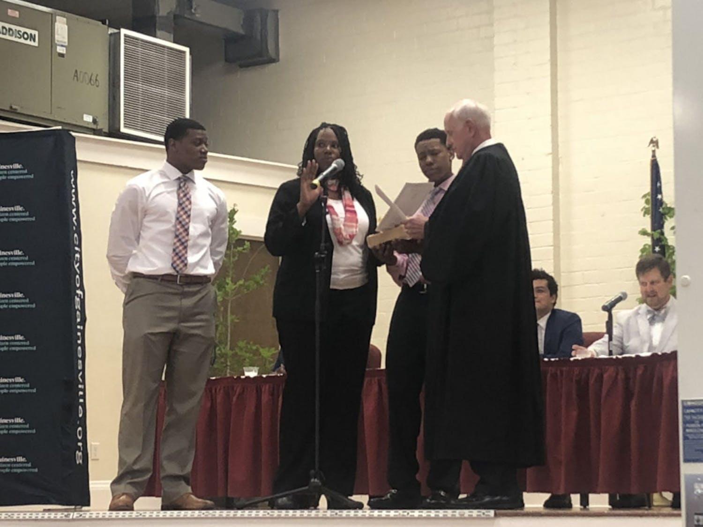 Gigi Simmons (center left) was sworn in alongside her sons Sterling (left) and Nicholas (center right).