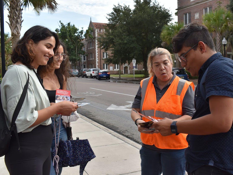 Paula Gonzalez, FDOT communication staff member, talks to students about pedestrian safety outside the UF chemistry building on Buckman Drive on Thursday, Aug. 26, 2021. (Photo by Elena Barrera)