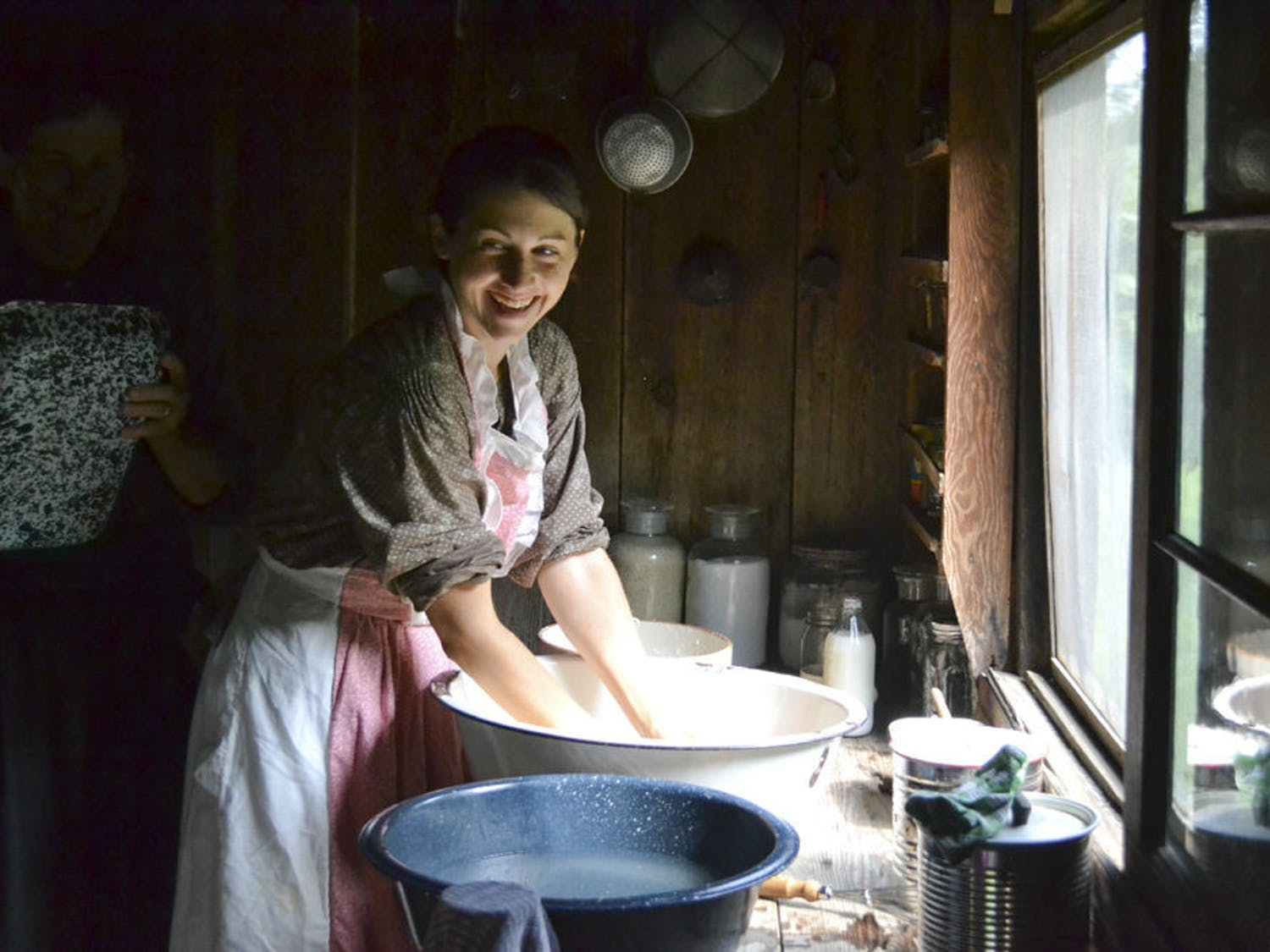 Val Leitner, 36, washes off homemade biscuit batter off her hands in a water bowl during the living history Reconstruction era event at Dudley Farm Historic State Park on Sept. 4, 2015. Leitner was participating as one of the living historians and cooked food for other volunteers on a wood stove.