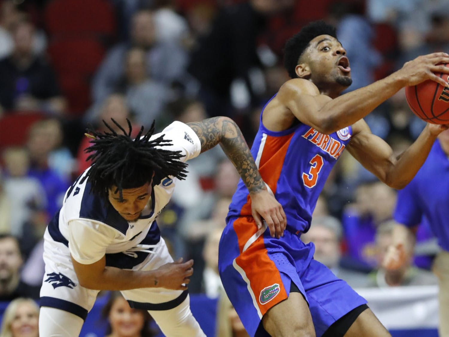 Florida guard Jalen Hudson (right) grabs a loose ball over Nevada guard Jazz Johnson during the Gators' 70-61 win in the First Round in the NCAA Tournament on Thursday in Des Moines, Iowa.