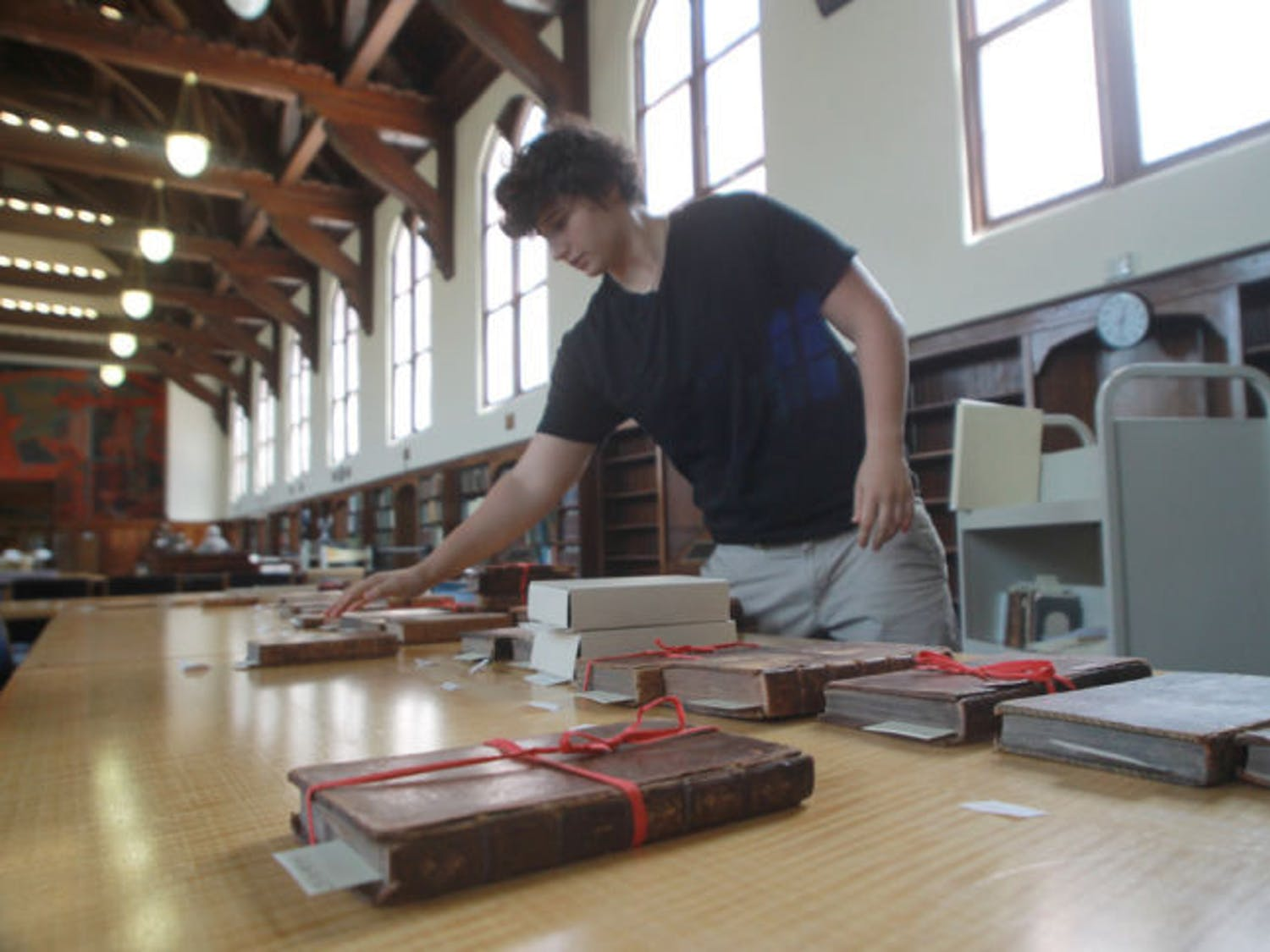 English senior Claudia Perlini, 22, sifts through a collection of 17th and 18th century children's literature in the University Archives in the George A. Smathers Libraries. The libraries were awarded funding from the National Endowment for the Humanities to digitize approximately 100,000 pages of historic newspapers.