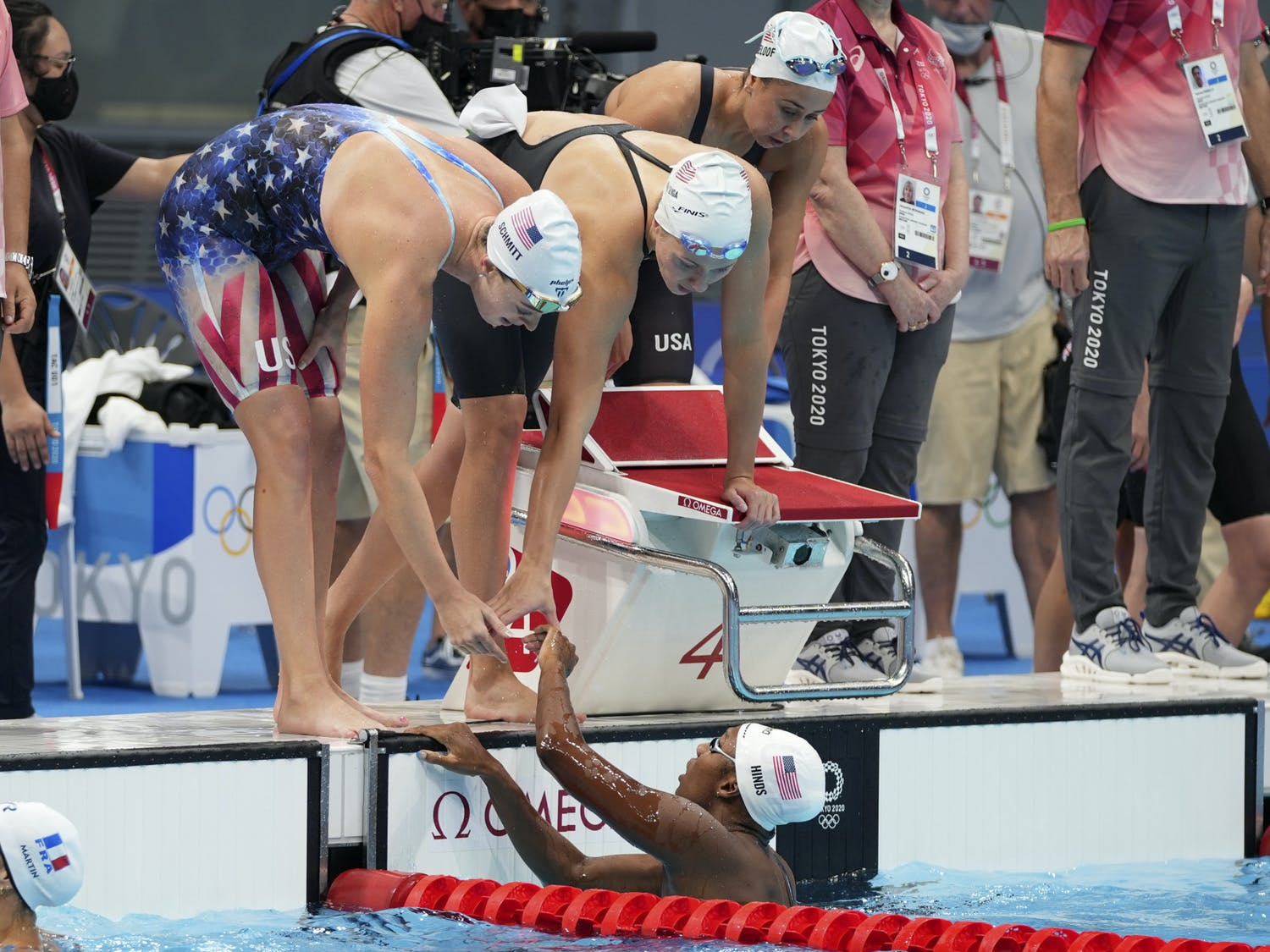 Natalie Hinds, bottom, of the United States is congratulated by teammates after swimming the fourth leg during a preliminary round of the women's 4x100m freestyle relay at the 2020 Summer Olympics, Saturday, July 24, 2021, in Tokyo, Japan. (AP Photo/Matthias Schrader)