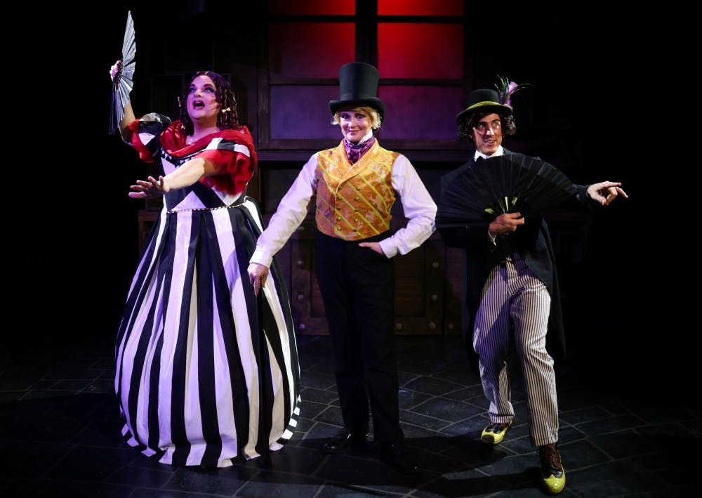 "<p>Actors Matthew McGee, Kelly Atkins and David Patrick Ford take center stage in costume for their roles in the Hippodrome's ""Scrooge in Rouge.""</p>"