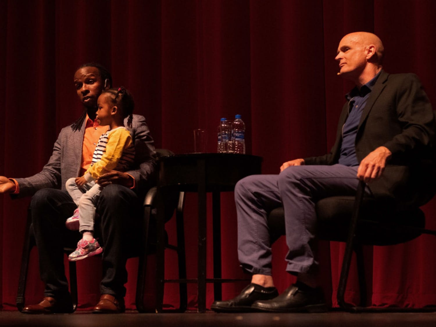 Ibram X. Kendi answers an audience question during a question and answer session moderated by author and history professor Jack Davis while Kendi's daughter sits in his lap at the Phillips Center for the Performing Arts Thursday night. About 1,230 people attended the event.