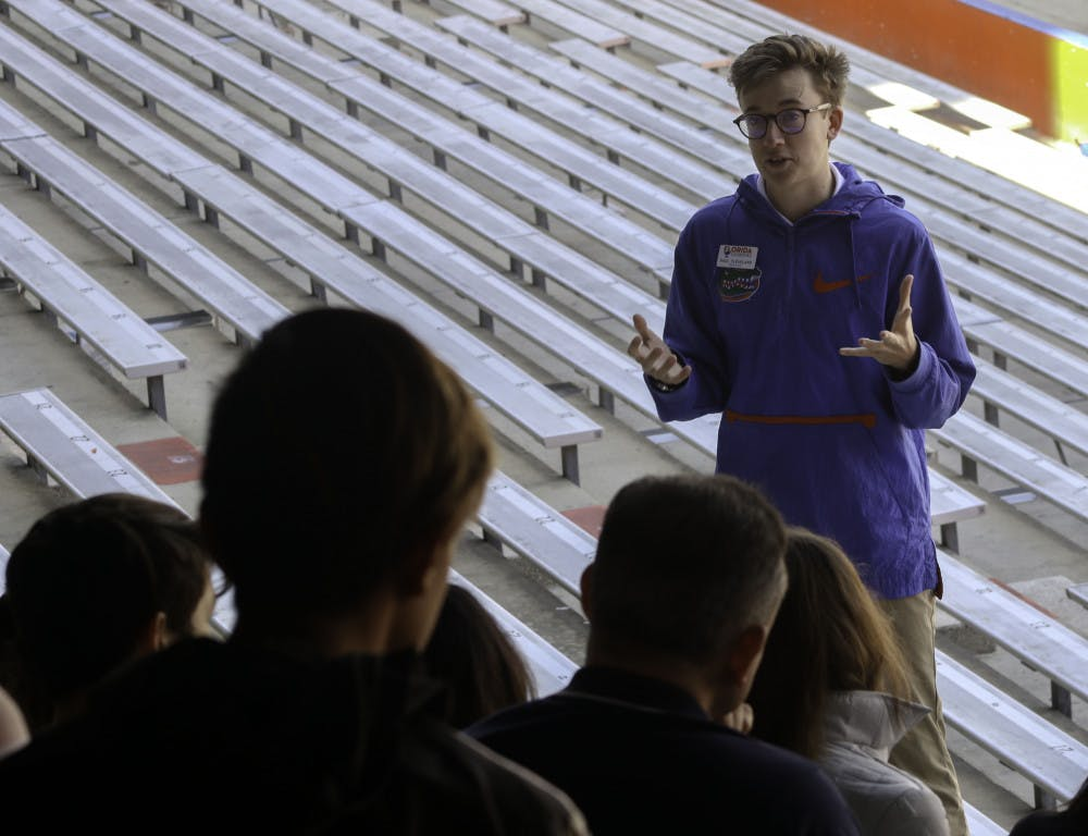 <p>Paul Cleveland, a 20-year-old UF economics junior and Cicerone, talks to a tour group in The Swamp about the football program at the school on Friday. Chris Day / Alligator Staff</p>