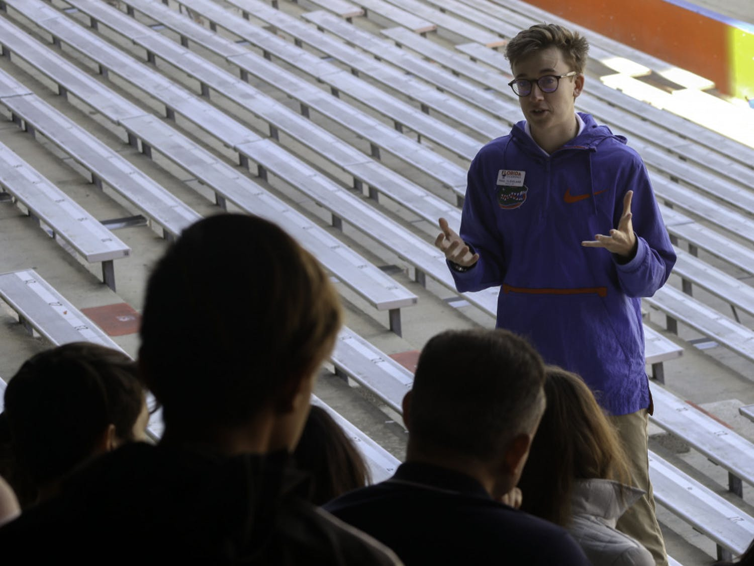 Paul Cleveland, a 20-year-old UF economics junior and Cicerone, talks to a tour group in The Swamp about the football program at the school on Friday. Chris Day / Alligator Staff