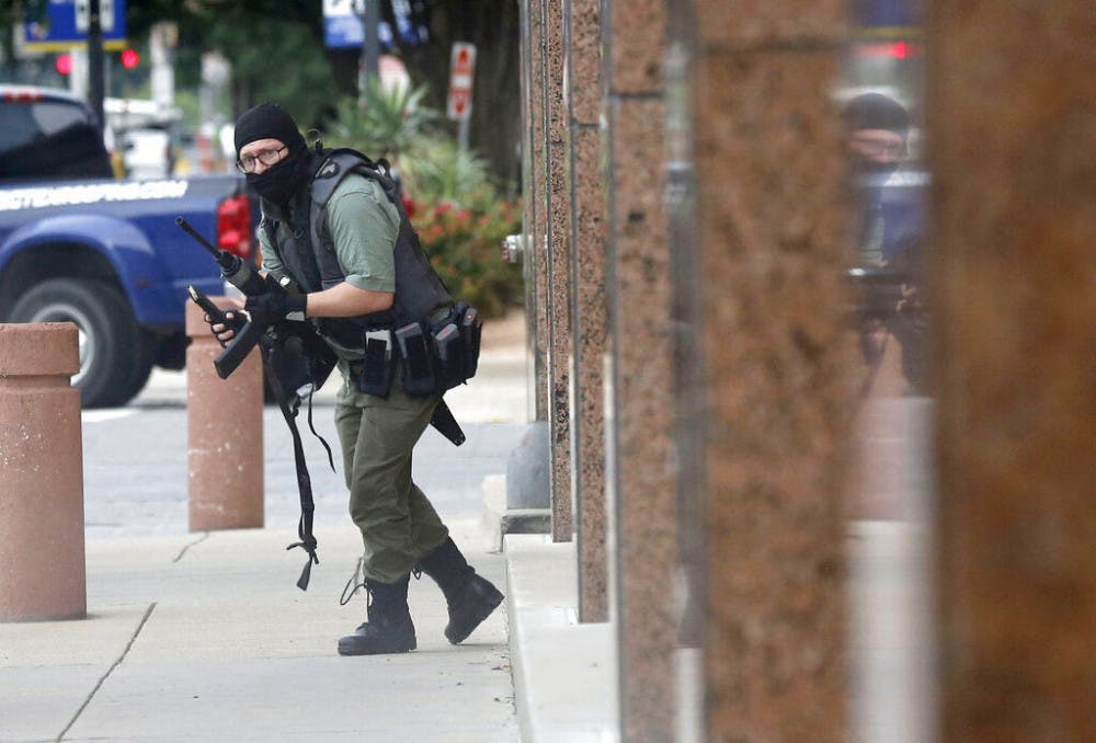 <p>An armed shooter stands near the Earle Cabell Federal Building Monday, June 17, 2019, in downtown Dallas. The shooter was hit and injured in an exchange of gunfire with federal officers outside the courthouse.&nbsp;</p>
