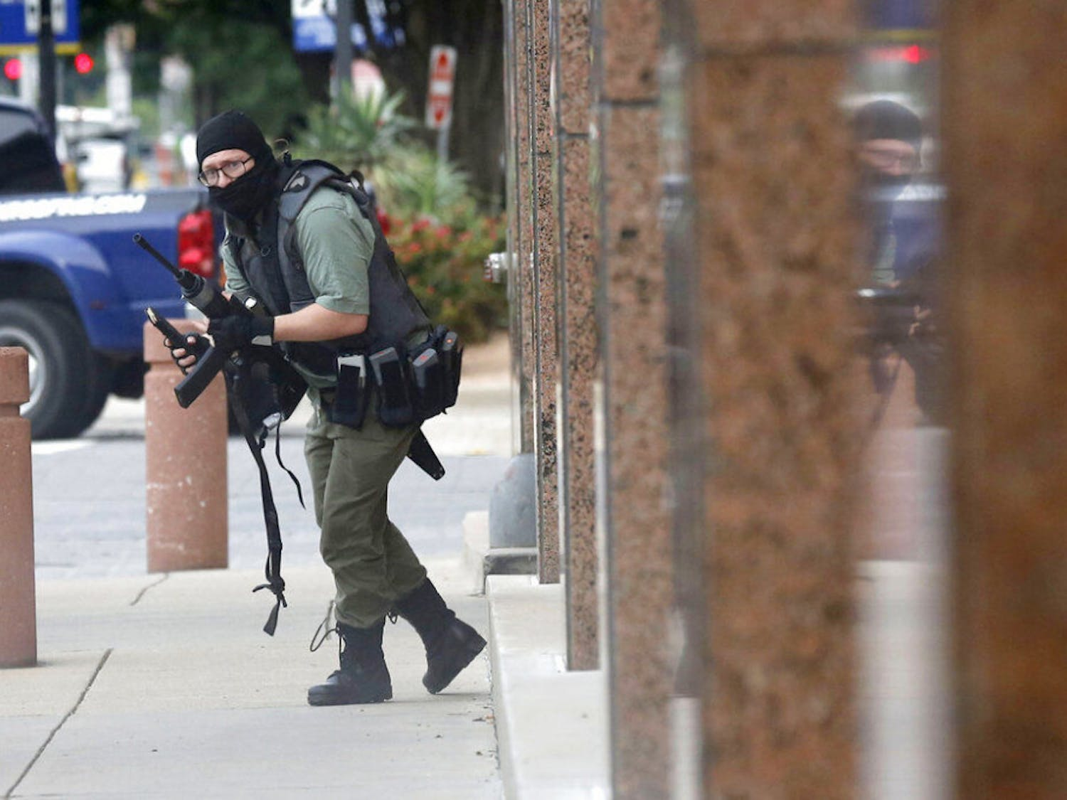 An armed shooter stands near the Earle Cabell Federal Building Monday, June 17, 2019, in downtown Dallas. The shooter was hit and injured in an exchange of gunfire with federal officers outside the courthouse.
