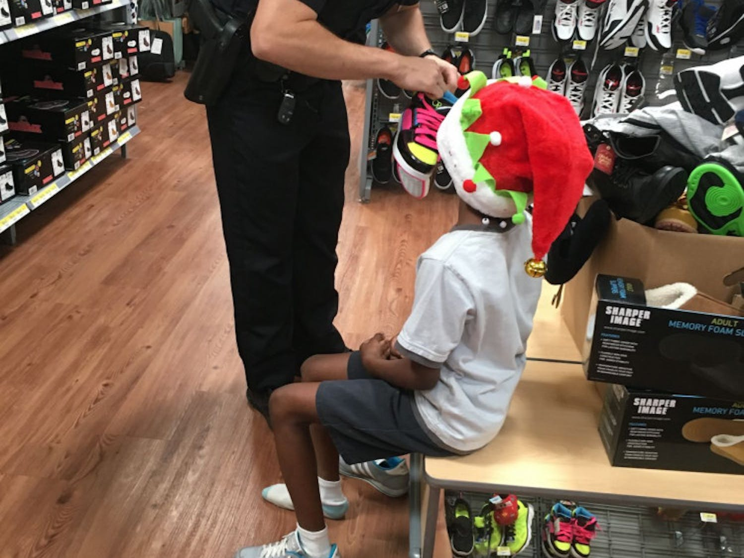 Ryan Quinn, Gainesville Police Department, helps 9-year-old Krystal Smith pick out a new pair of shoes.