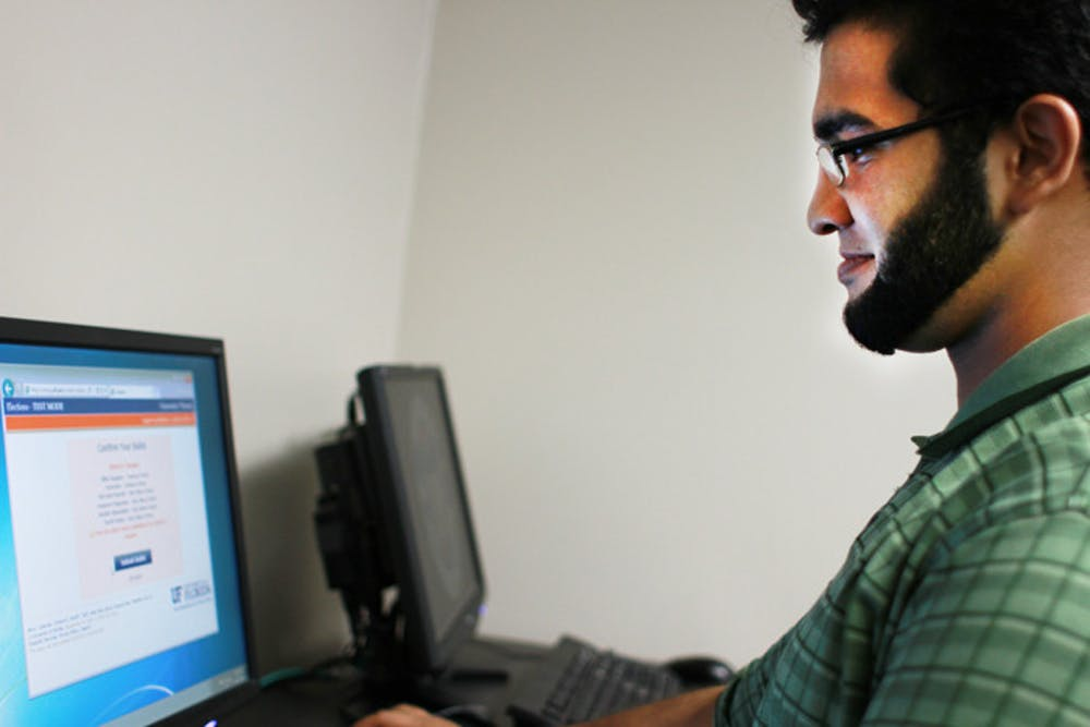 <p>Umair Asghar, an 18-year-old mechanical engineering sophomore, tests the new electronic voting system. Senators chose candidates from the Star Wars Party and the Fantasy Party.</p>