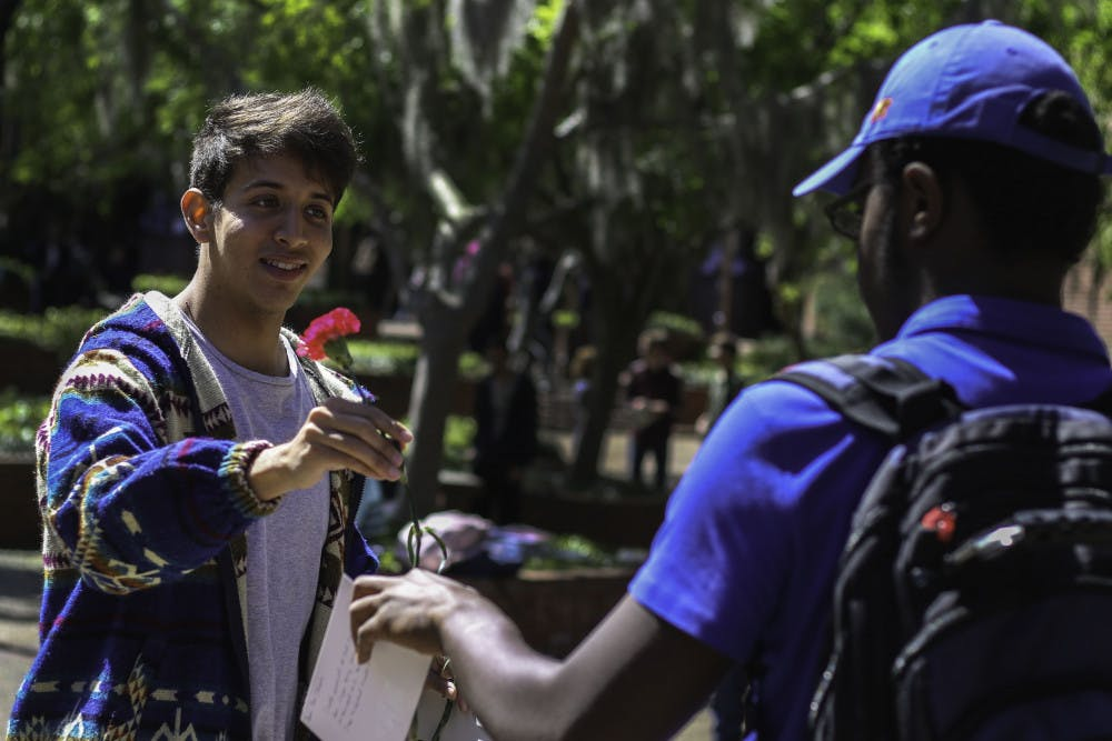 """<p dir=""""ltr""""><span>Matthew Diaz, a 21-year-old political science third year, hands a rose and thank you card Monday to Shameer Boursiquot, an 18-year-old aerospace engineering first year, to give to a bus driver for the RTS Driver Appreciation event. """"I ride the bus nearly every day to and from school, and it's always been something I'm really grateful for,"""" Diaz said.</span></p><p><span></span></p>"""