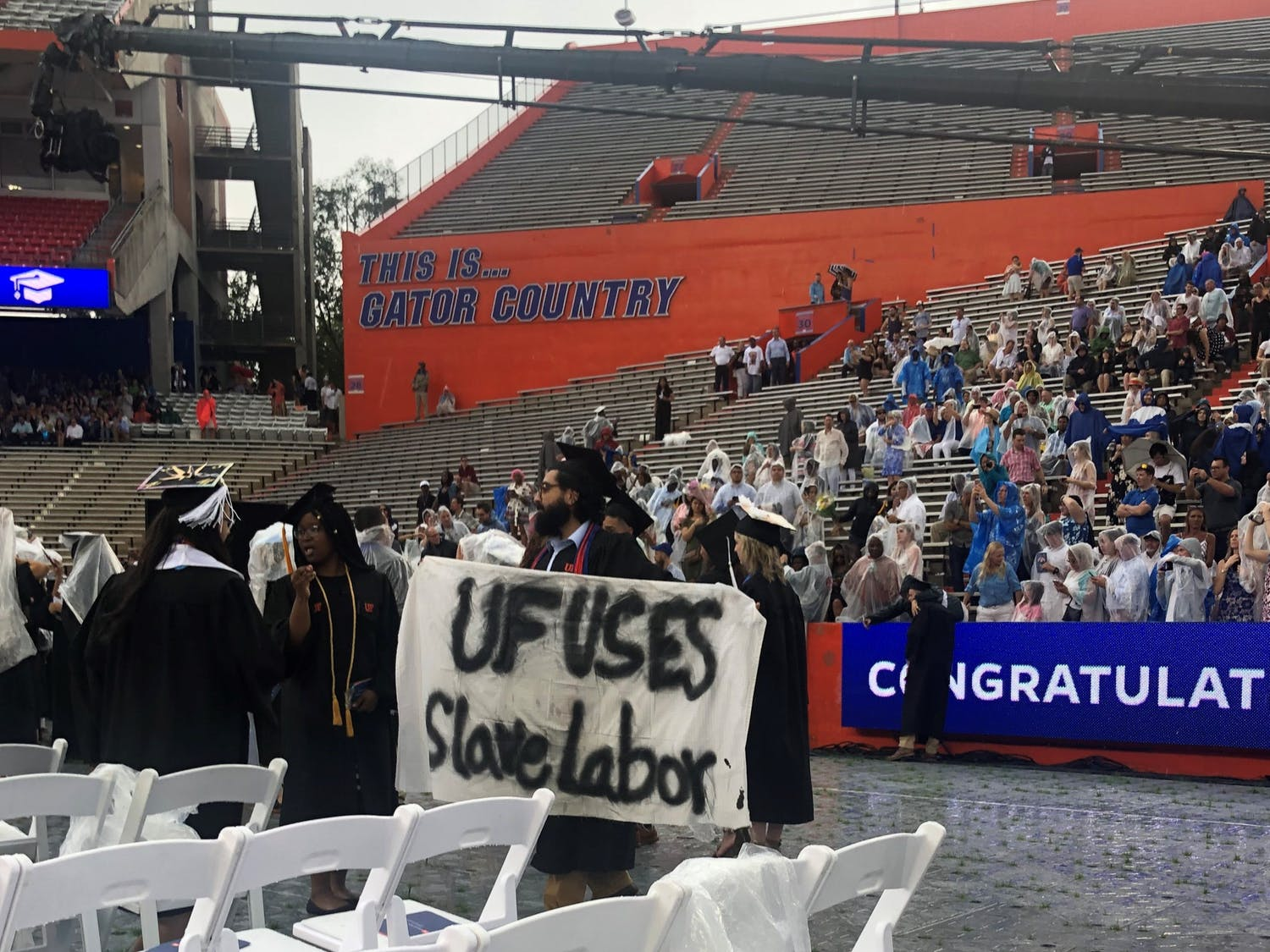 Syed Muhammad Omar holds a banner during the College of Liberal Arts and Sciences commencement ceremony on Sunday. Omar, a 27-year-old UF psychology bachelor's graduate, said he is involved with Divest UF.