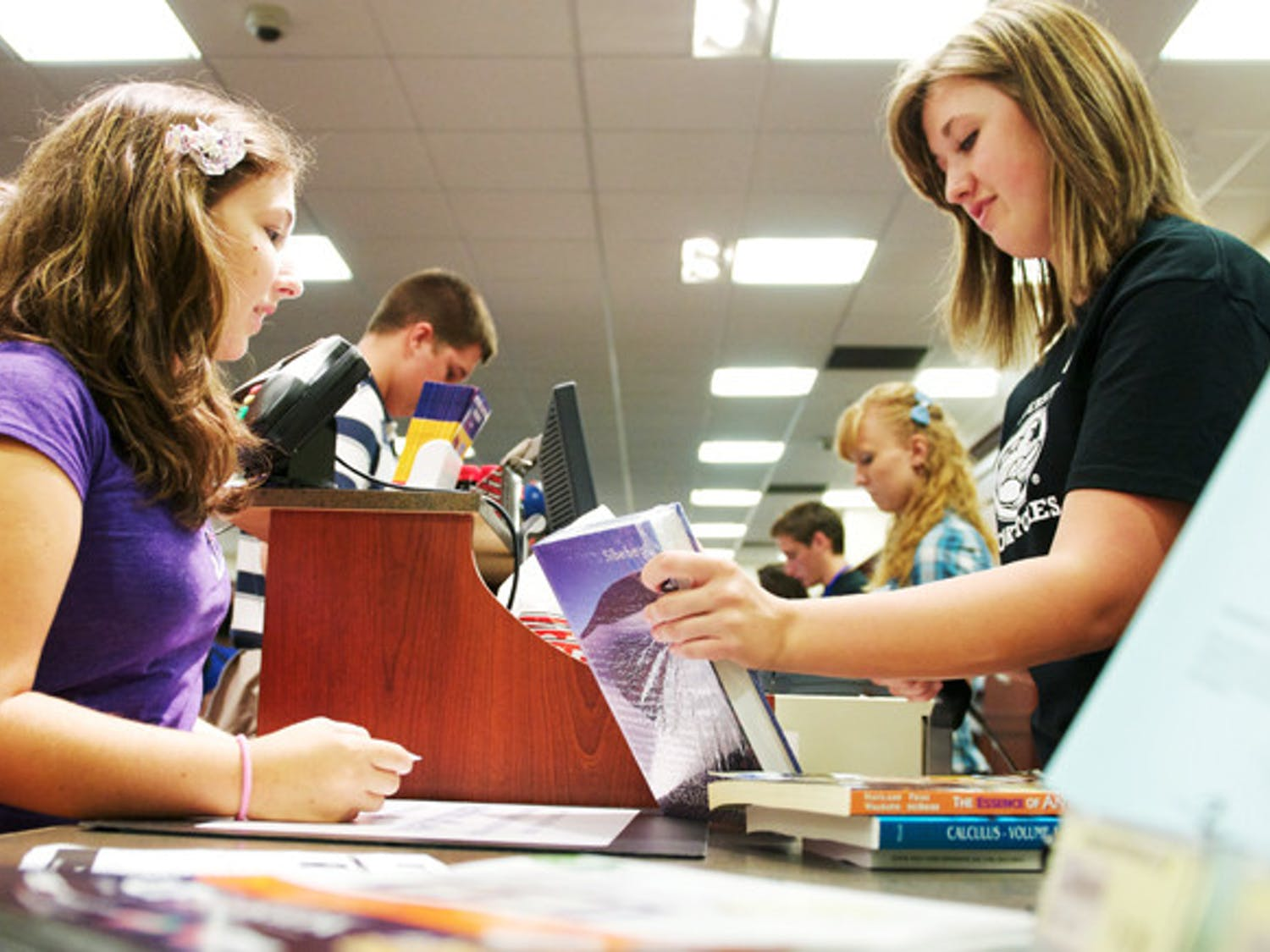 UF freshman Christina Lynch, left, purchases a textbook at the UF Bookstore inside the Reitz Union on Thursday, Aug. 22, 2011.