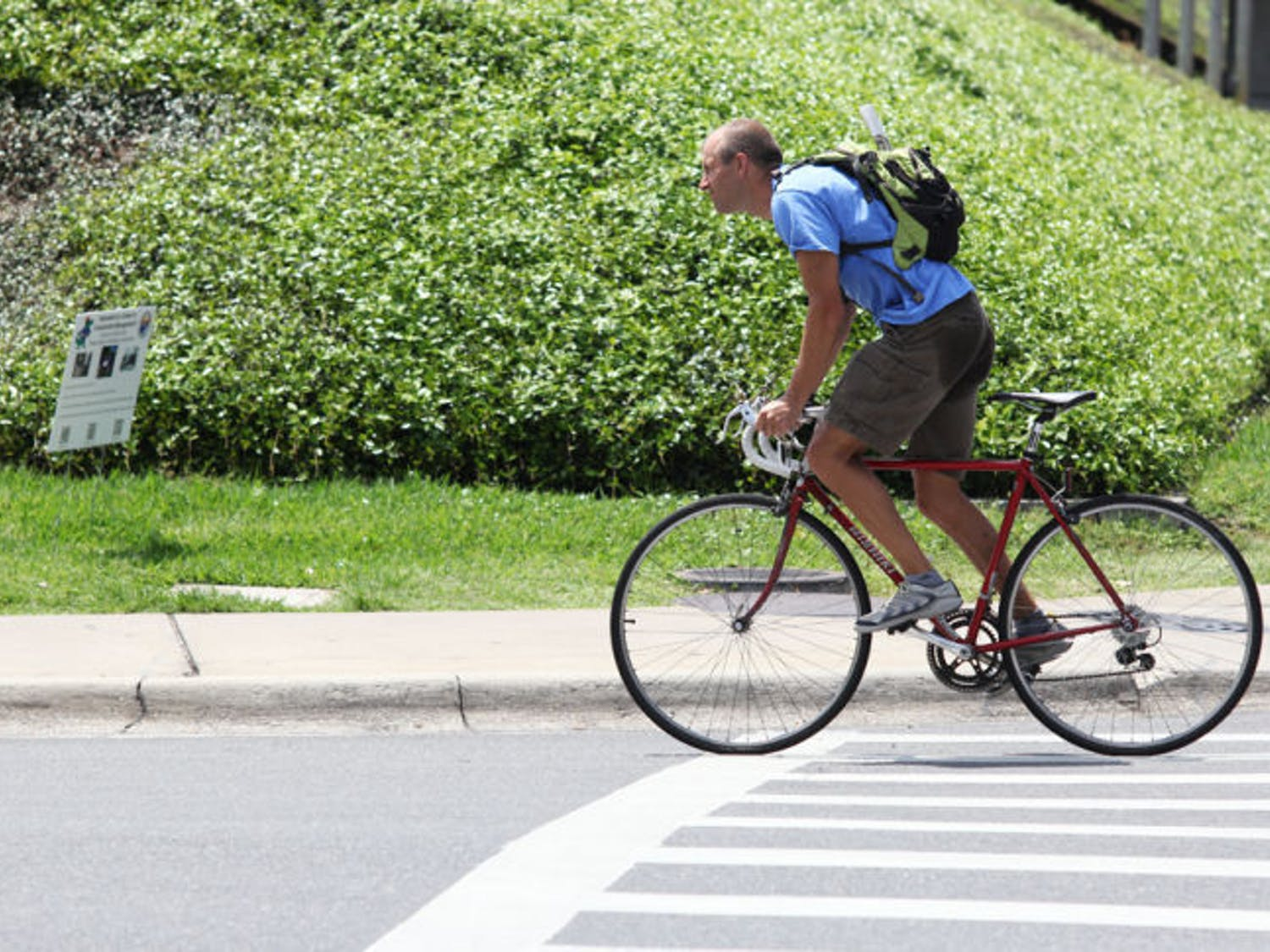 A commuter rides his bike east on Museum Road on Monday afternoon. A new study shows that biking to work can be healthier than regular exercise.