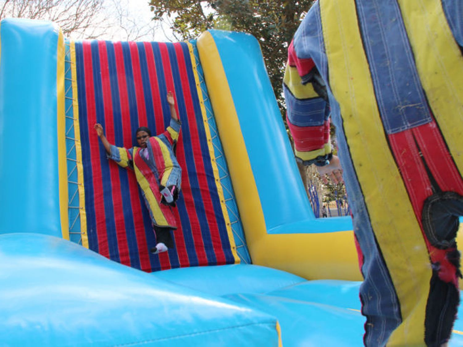 First-year acting graduate student Oluchi Nwokocha, 23, descends from a Velcro wall on the North Lawn Tuesday afternoon. The wall was part of UF Engineers Week's Field Day Extravaganza.