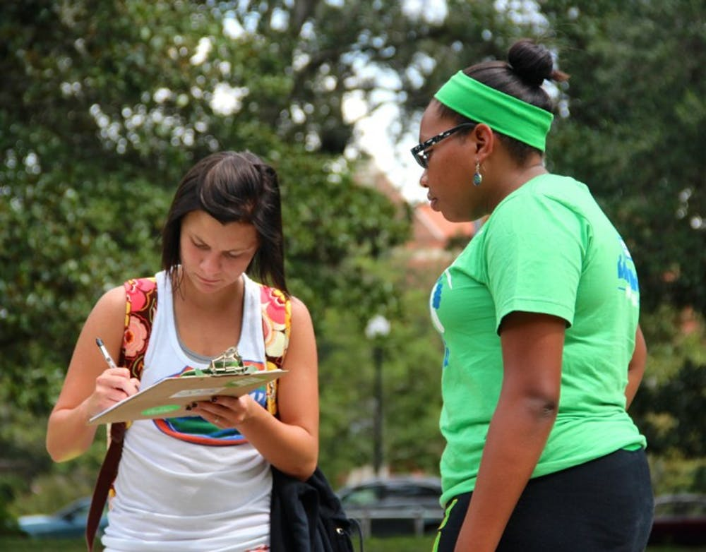 """<p>Brittany Bowen, 18, left, fills out a pledge card while Janine Monfries, 21, helps with the """"Power Vote"""" campaign on the Plaza of the Americas on Thursday.</p>"""