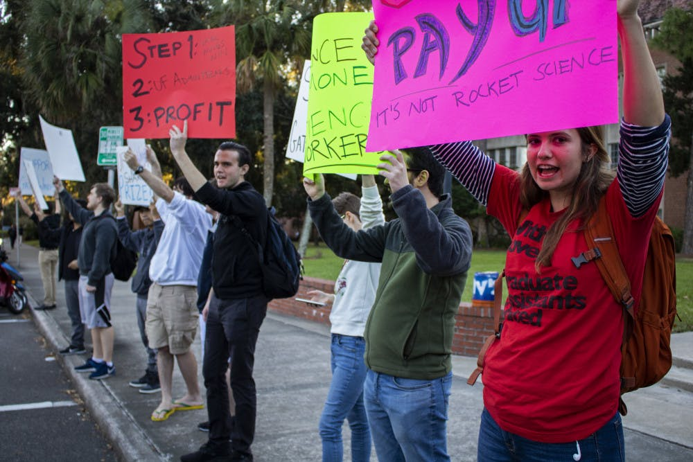 """<p dir=""""ltr"""">Bobby Mermer, a 32-year-old political science doctoral student and co-president of Graduate Assistants United, leads a chant Tuesday afternoon during the GatorWings Support Rally. The rally was held outside of Tigert Hall with 12 people in attendance.</p>"""