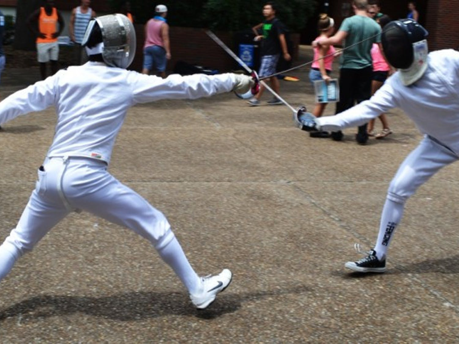 Get the point? - Gavin O'Leary (left), a 19-year-old nuclear engineering sophomore, and Eric Massa (right), a 20-year-old biology junior, duel on Turlington Plaza to recruit new members for the Fencing Team. The club has about 50 members, travels frequently and uses weapons called sabers, foils and epees.